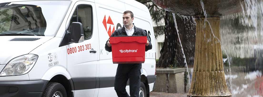 Hombre con caja roja junto a furgoneta