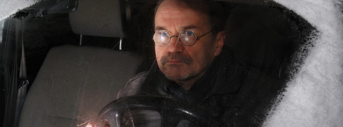 hombre en el interior de un coche congelado