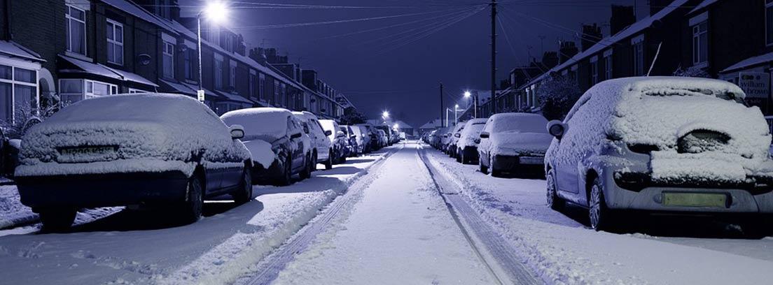 varios coches aparcados con nieve sobre ellos