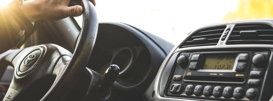 Mano en un volante de coche.