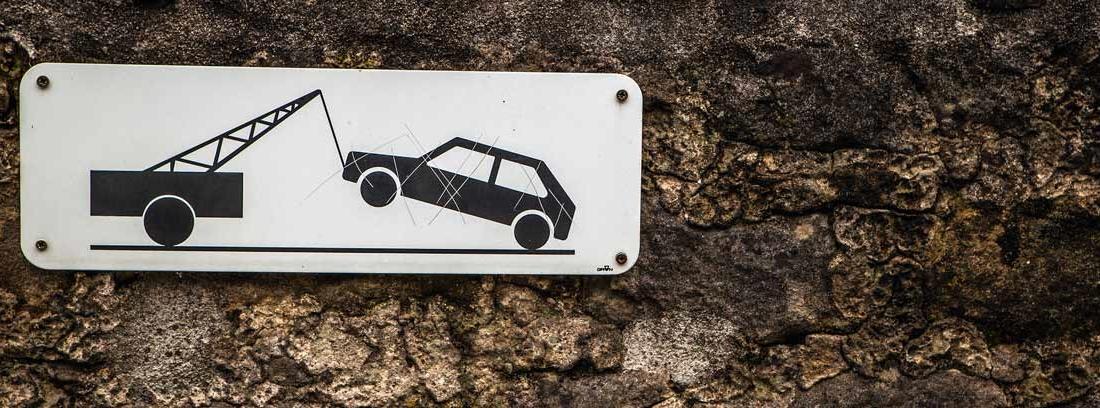 : Letrero informativo en el que se ve una grúa llevándose un coche