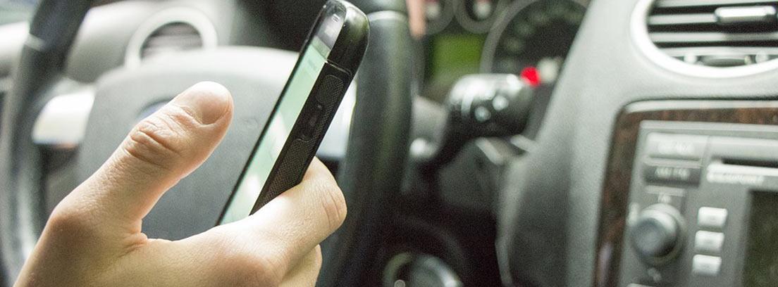 persona usando el teléfono móvil en el coche