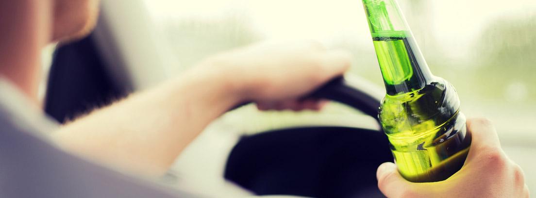 Hombre dentro de un coche con una mano en el volante y otra en un botellín de cerveza