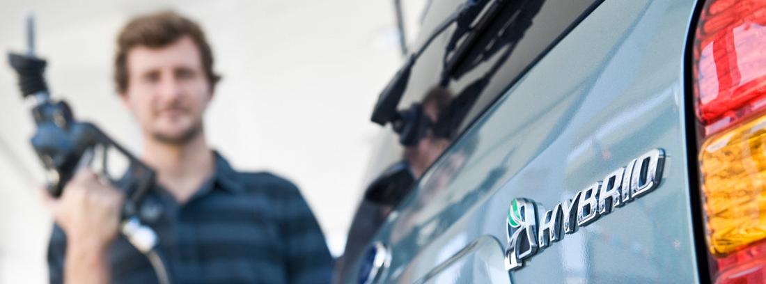 Hombre con manguera en la mano para cargar su coche híbrido enchufable