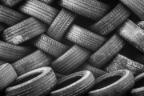 Neumáticos de coche gastados y sucios apilados formando una pared
