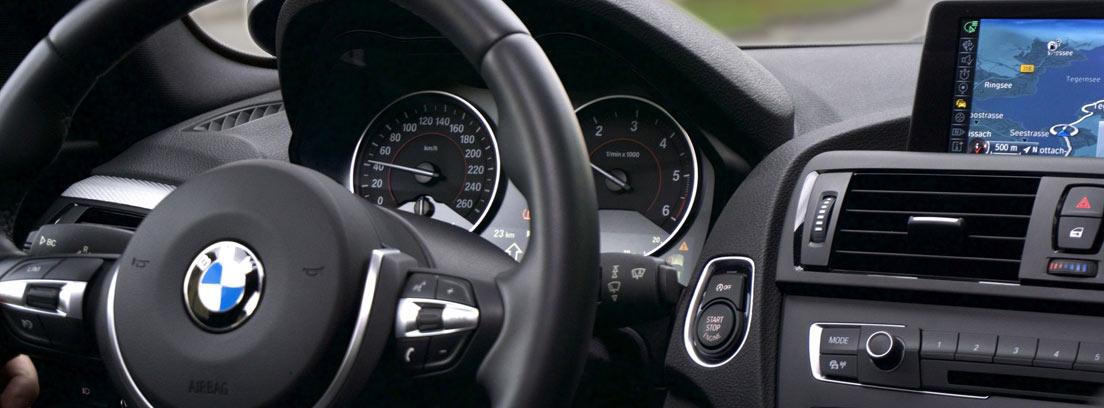 Volante de coche, cuadro con velocímetro y navegador en el salpicadero