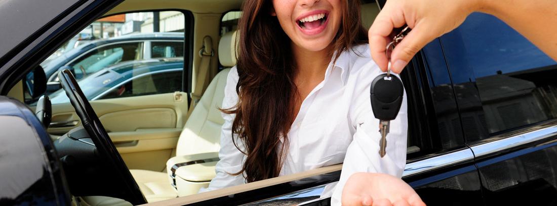 Vendedor entrega llave a una mujer dentro de un coche en un concesionario
