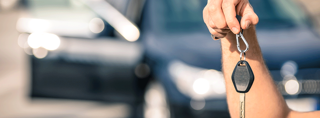 Mano de hombre con unas llaves y un coche al fondo