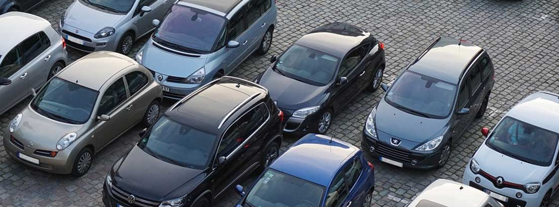distintos tipos de coche en un aparcamiento
