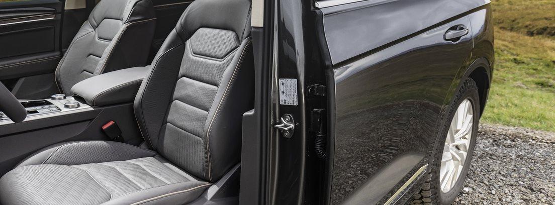Vista interior de los asientos delanteros del Volkswagen Touareg V8 TDI con la puerta del conductor abierta