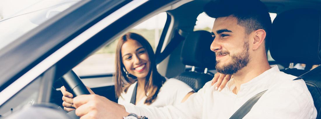 Una pareja sonriente en un coche