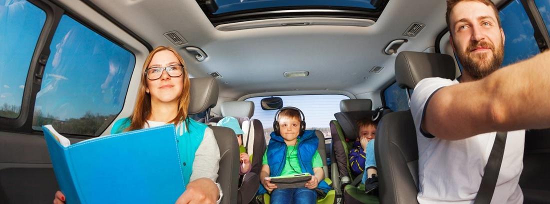 Hombre, mujer y niños acomodados en el interior de un vehículo espacioso.