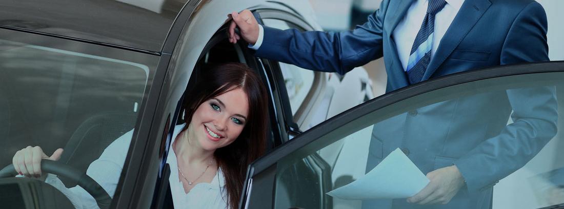 Mujer dentro de coche y hombre junto a la puerta abierta.