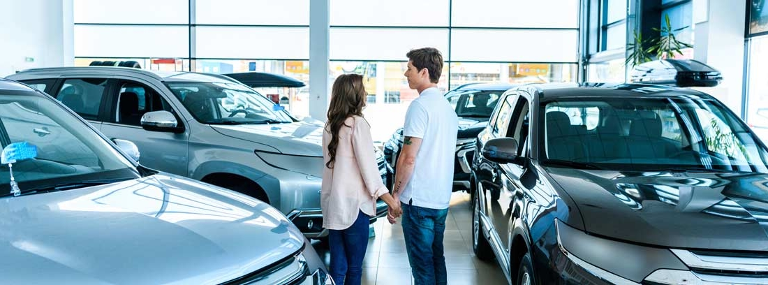 Hombre y mujer entre diferentes coches en un concesionario de segunda mano.