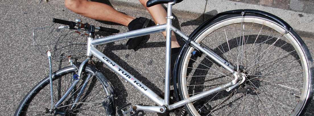 Piernas de hombre sobre la acera y bicicleta en el suelo junto a él