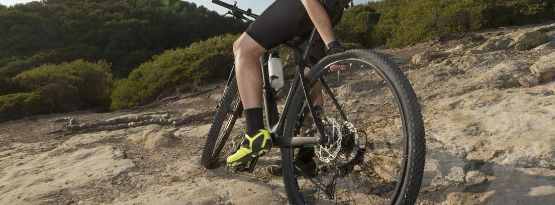 Ciclista toca la rueda posterior de su bici