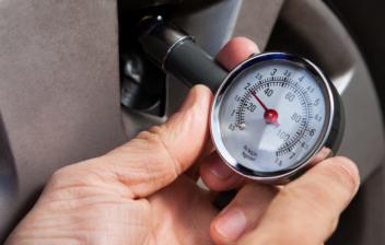 Mano comprobando con un manómetro la presión de los neumáticos