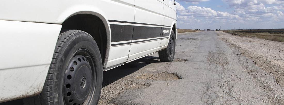 Vista parcial de la rueda con amortiguadores de gas sobre una carretera con irregularidades