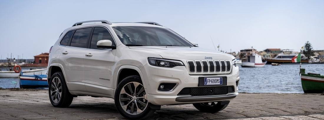 Jeep Cherokee blanco estacionado en un puerto