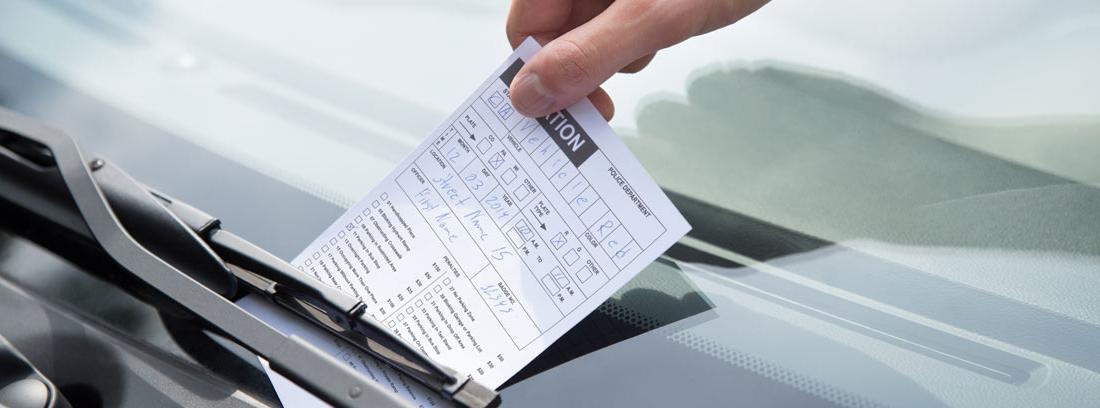 Mano cogiendo una notificación de una multa de un parabrisas de un coche