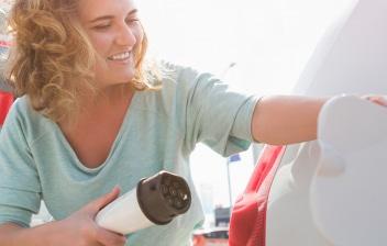Mujer cargando un coche eléctrico