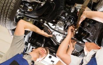 Dos mecánicos trabajando bajo un coche