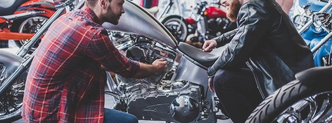 Dos hombres agachados junto a una moto