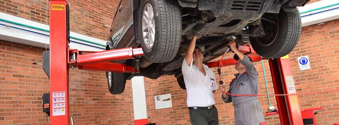 dos mecánicos revisando los bajos de un coche