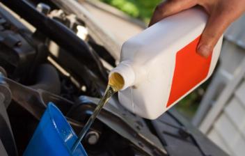 Mano echando aditivo de aceite sobre embudo en motor de coche.