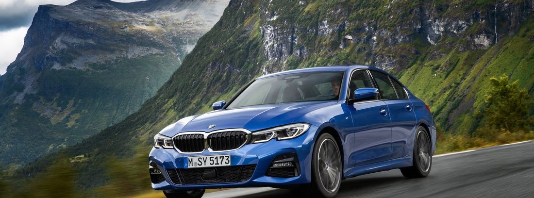 Vista delantera del nuevo BMW Serie 3 en color azul circulando entre montañas