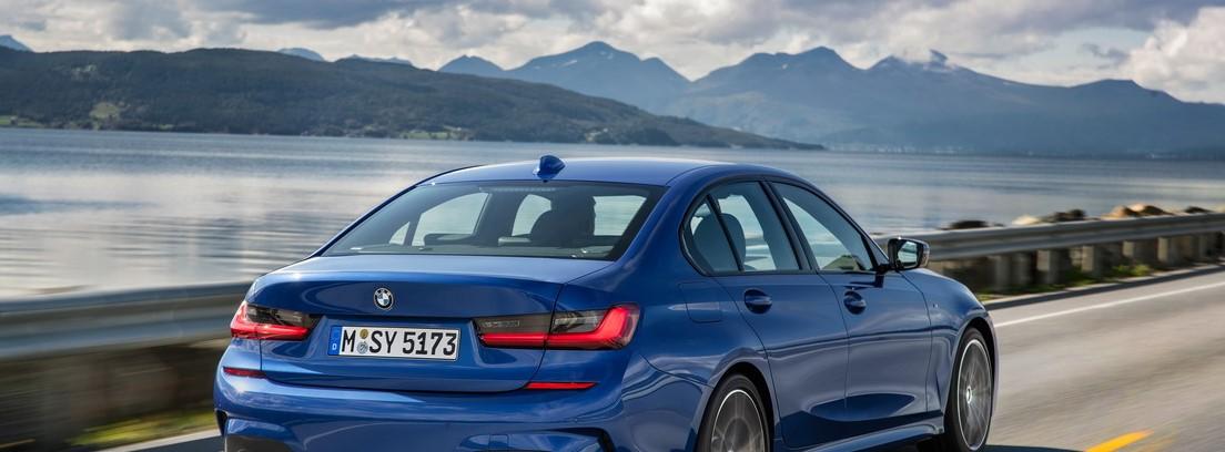 Vista trasera del nuevo BMW Serie 3 en movimiento con un fondo natural de lago