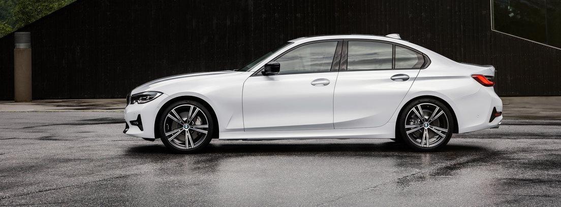 Vista lateral del nuevo BMW Serie 3 en color blanco sobre asfalto