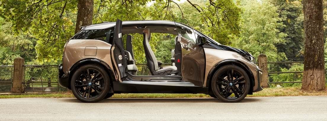 Vista lateral del modelo BMW i3 con todas sus puertas abiertas sobre fondo campestre