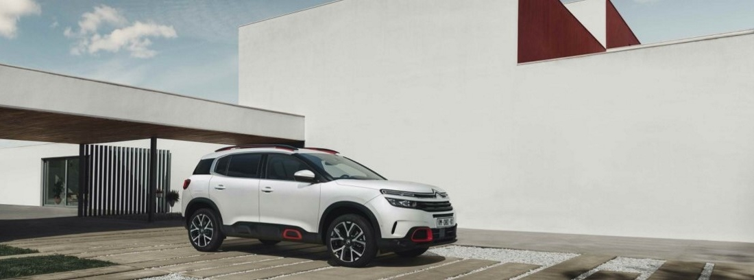Vista lateral derecha del coche Citroën C5 Aircross frente a muro blanco