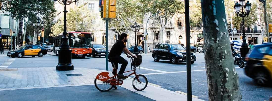 Vista general de cruce de calles en una ciudad con coches, autobuses y bicis.