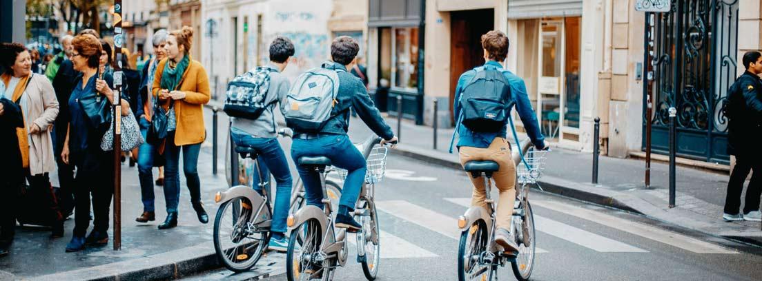Calle de ciudad con peatones y bicicletas.