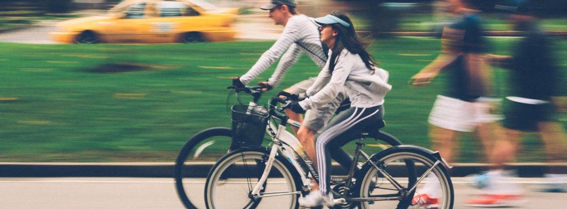 Dos personas en bici circulando por calle de ciudad