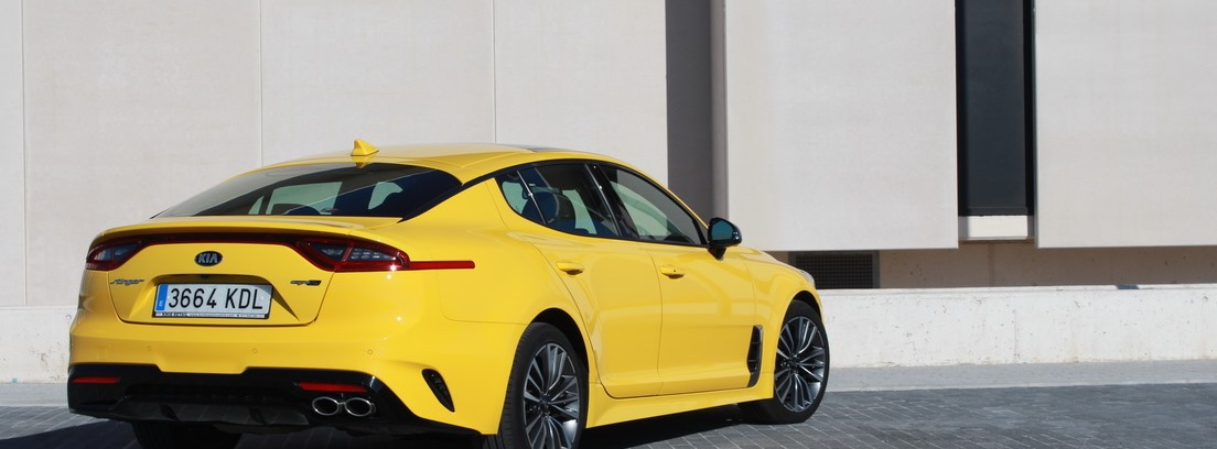 Kia Stinger amarillo estacionado frente a un edificio crema