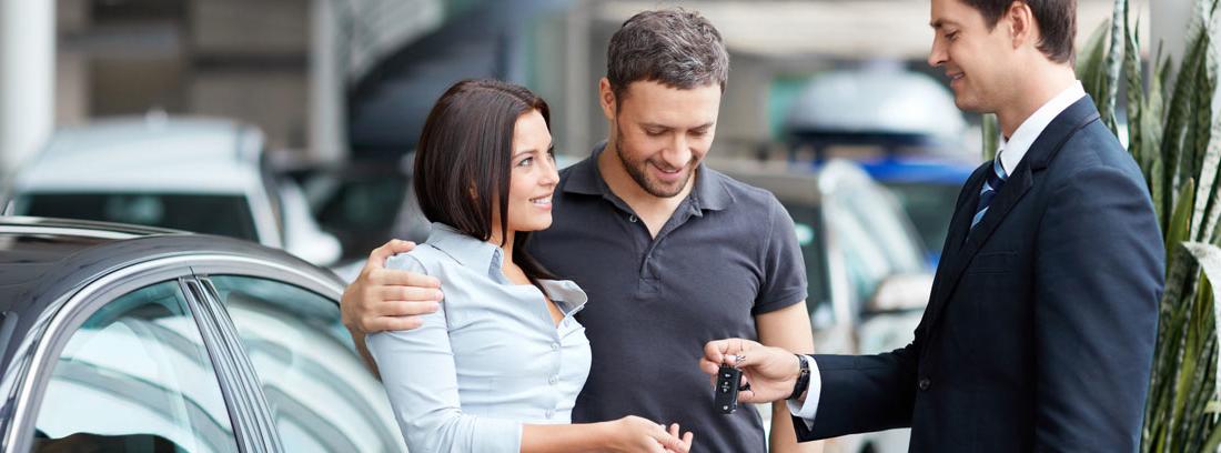 Hombre y mujer miran documentación de un coche en concesionario