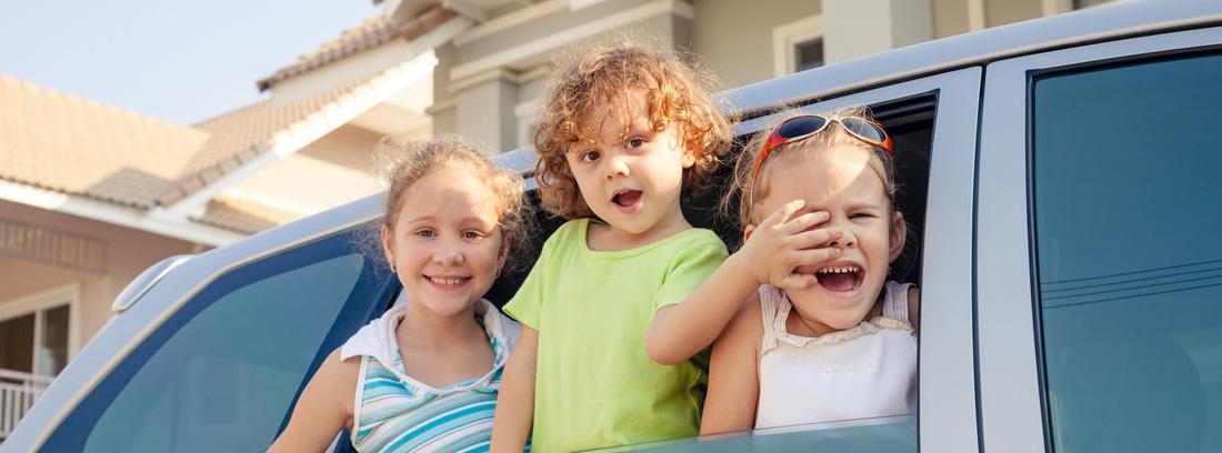 Tres niños felices asomados por la ventanilla de un coche