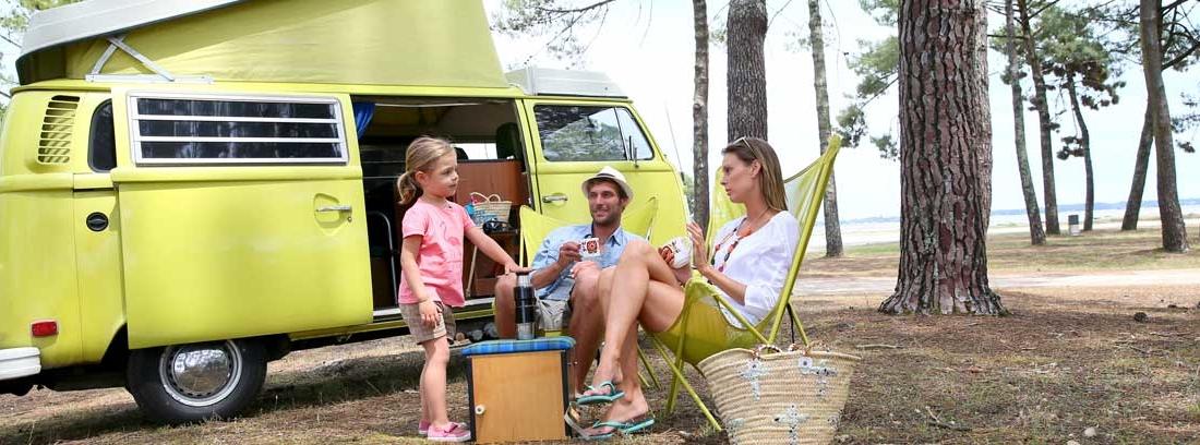 Familia sentada en el exterior de una furgoneta camper