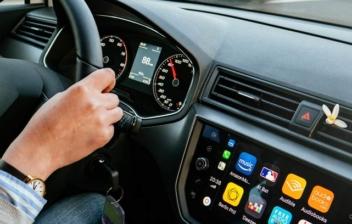 Mujer dentro de un coche con las manos en el volante, con el panel central encendido
