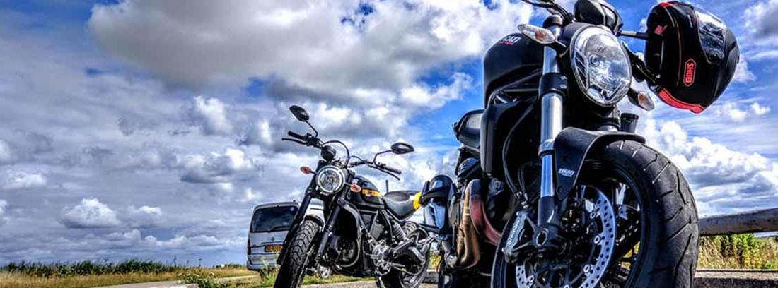 Sobre asfalto dos motos paradas con casco en el manillar