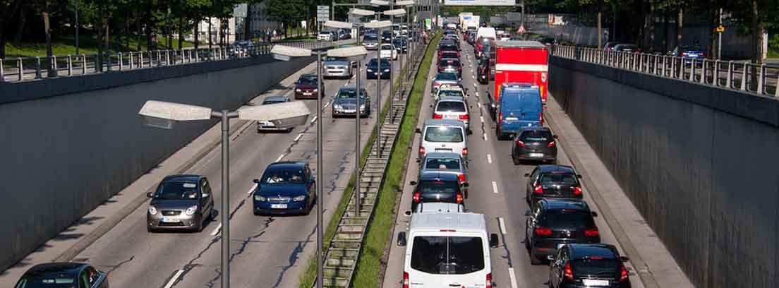 Carretera de doble sentido con mediana central y llena de coches.