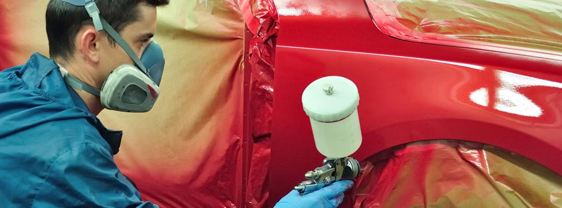 Hombre con mascarilla y aerosol pintando un coche con vinilo líquido rojo