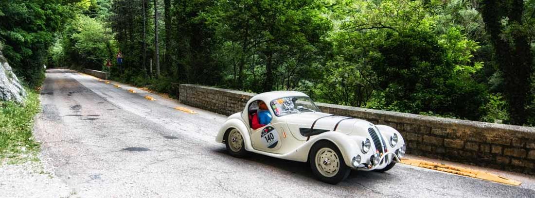 BMW 328 Coupe 1937 blanco participando en un rally de regularidad