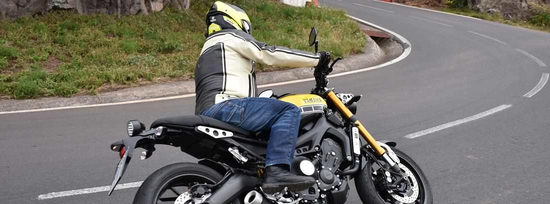 Persona sobre moto tomando una curva entre montañas