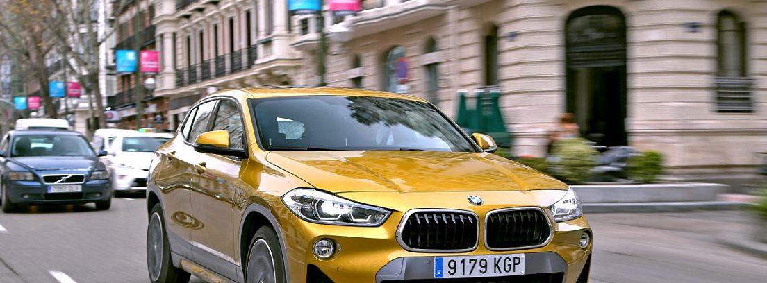BMW X2 amarillo circulando por ciudad