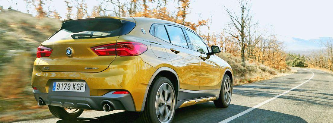 BMW X2 amarillo circulando en una carretera secundaria
