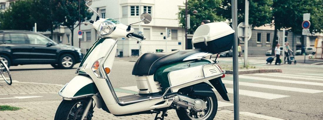 Moto de color blanco aparcada en una acera en ciudad